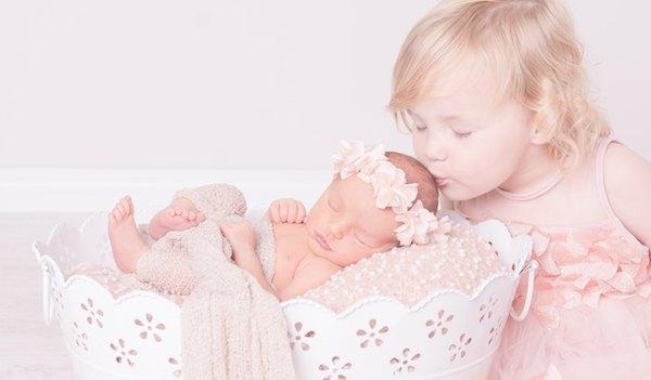 Neugeborenes mit großer Schwester, ganz verliebt