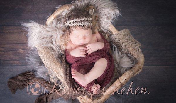 Neugeborenes Mädchen in weichem Körbchen